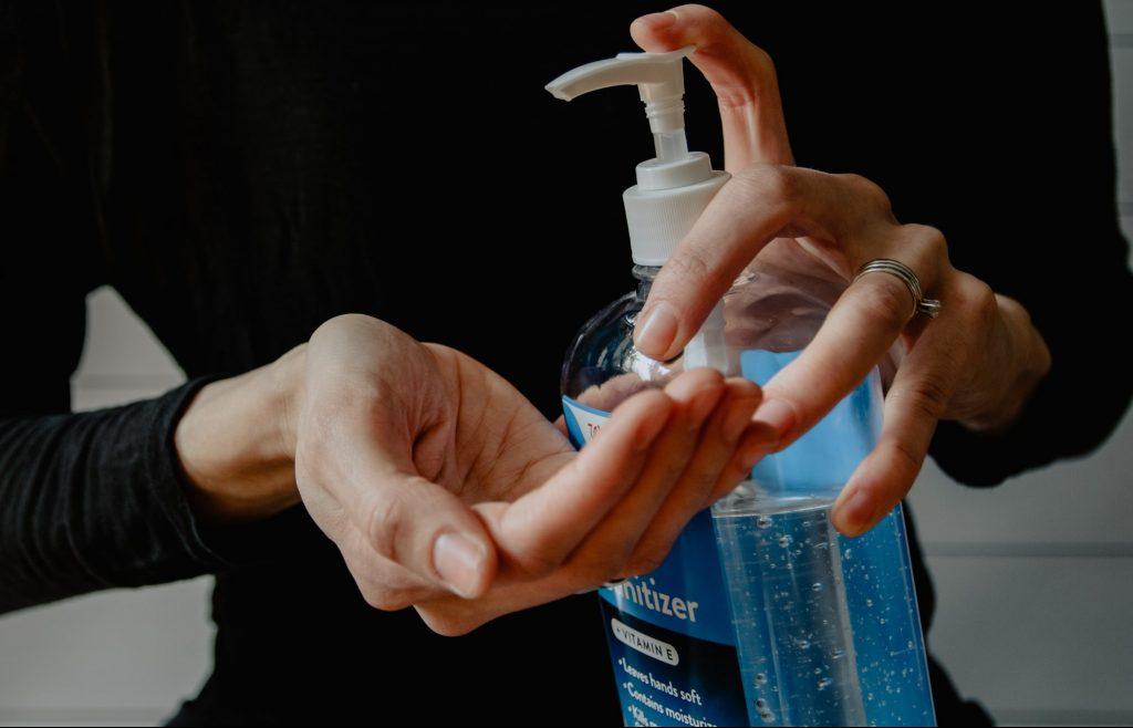 Woman applying hand gel from a pump bottle