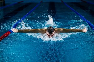 Man butterfly swimming in blue swimming pool