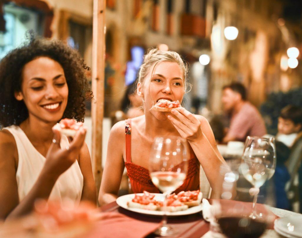 Women eating bruschetta, a customer in a restaurant